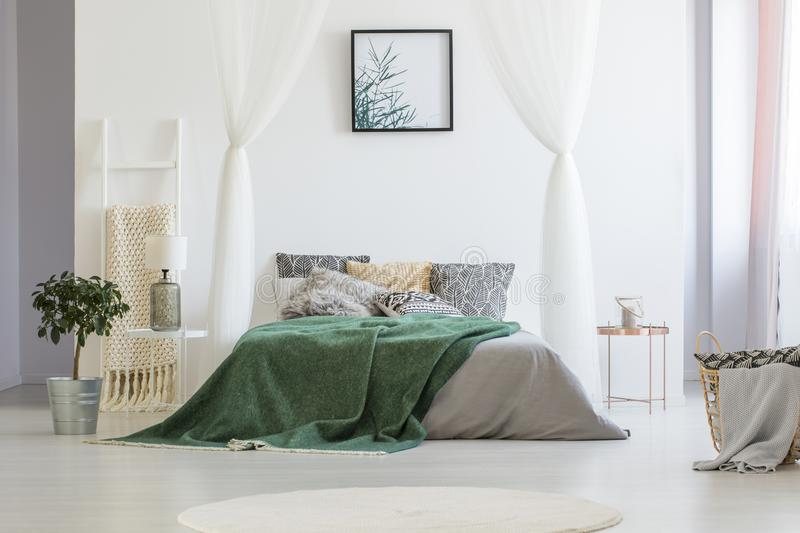 Green blanket thrown on double bed with many pillows and grey sh royalty free stock photo