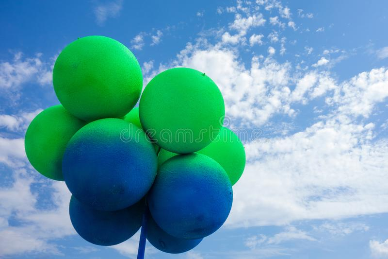 Green and blue balls balloons on cloud sky background. Vivid holiday poster with copy space. Sunny happy day concept stock images