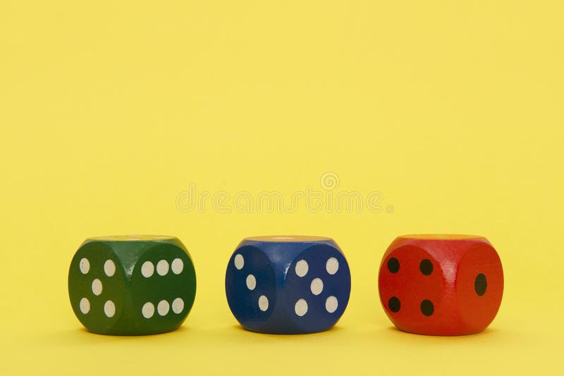 Green, blue and red dice in a row on a yellow background with sp stock photo
