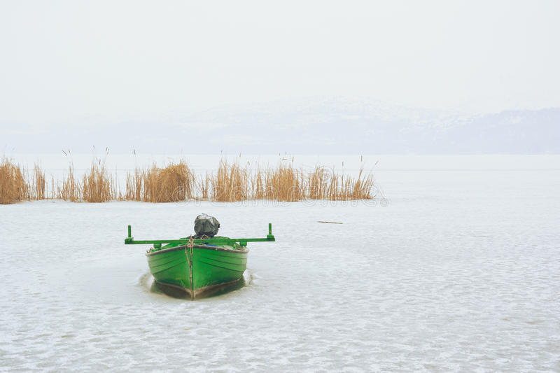 Green boat trapped in frozen lake royalty free stock image