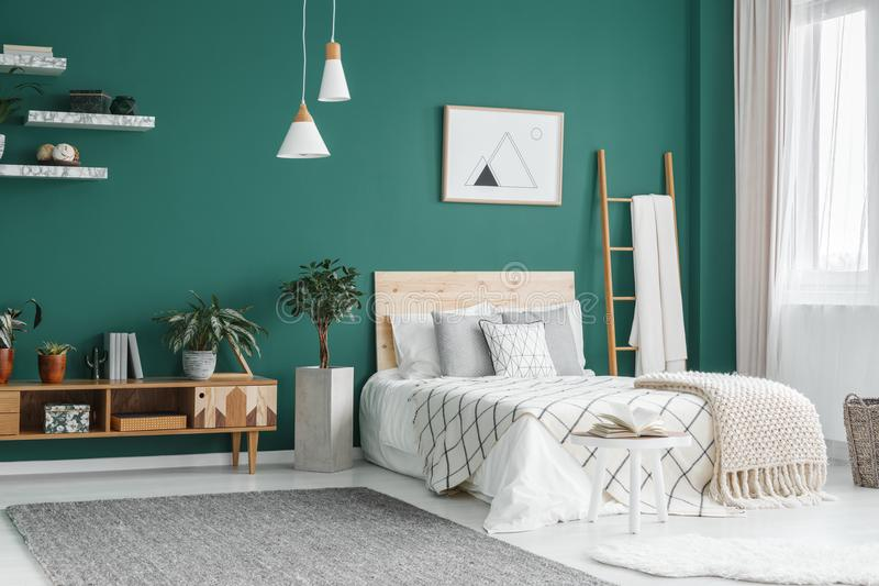 Green boho bedroom interior. Bed between ladder and plant in green boho bedroom interior with grey carpet under lamps royalty free stock image