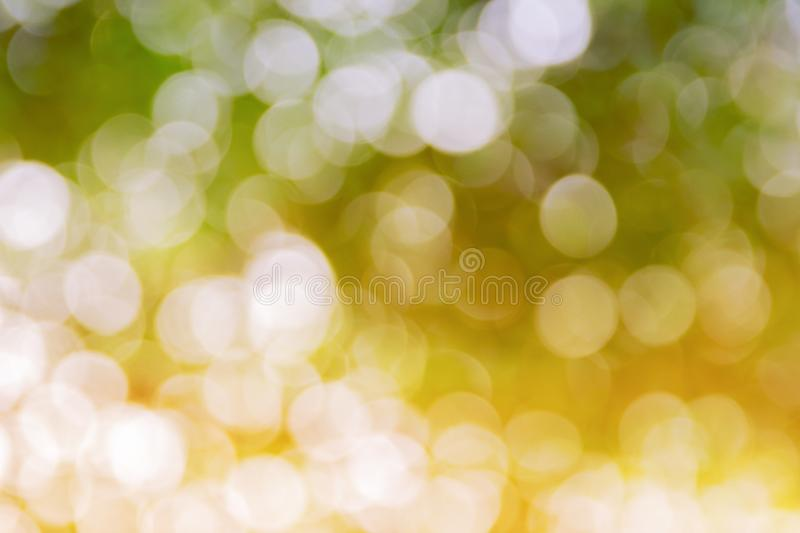 Green bokeh natural color abstract blurred background Warm leaf of tree and bright summer sunlight.  royalty free stock images