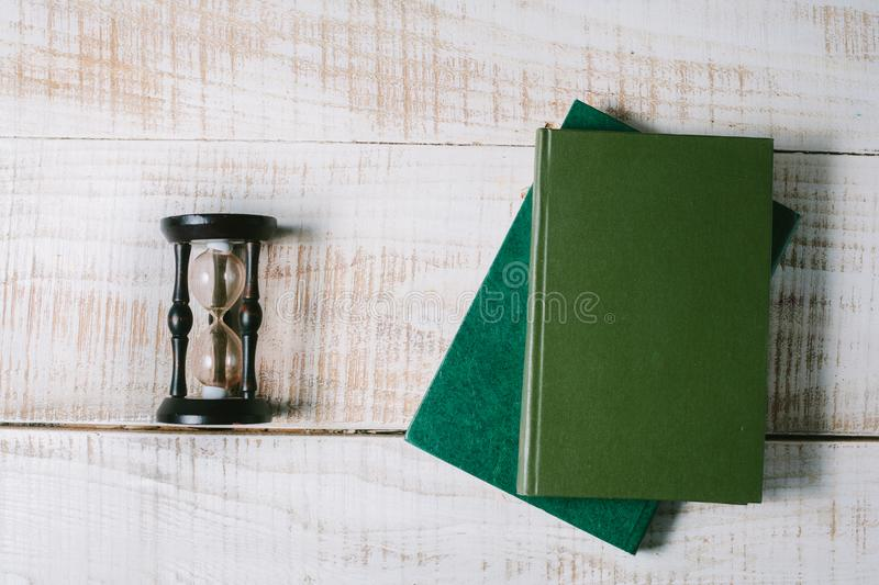 Green books and hourglasses lie on a wooden table. top view royalty free stock photos