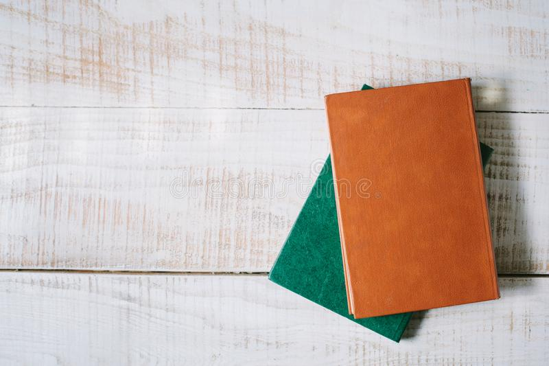 Green books lie on a wooden table. top view. layflat stock photo