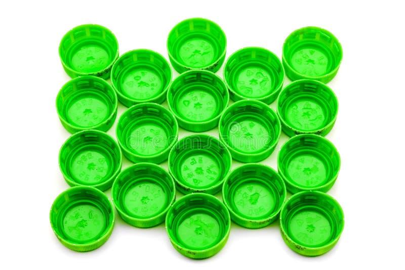 Green bottle caps. Group of green bottle caps against white surface stock image