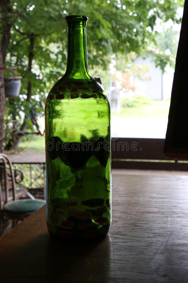 The green bottle on the table by the window. The light brightens the view with the green bottle on the table royalty free stock images