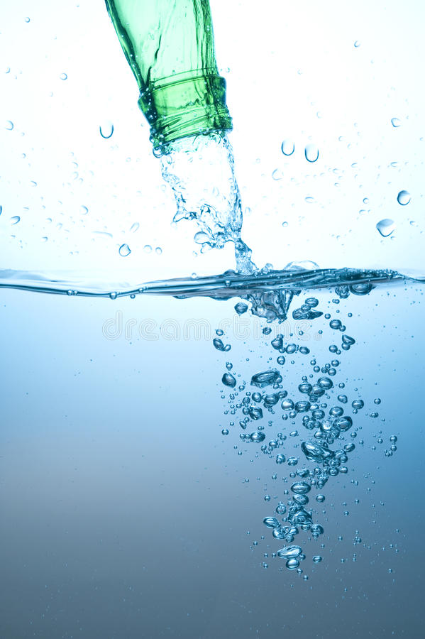 Green bottle and water splashing stock photography