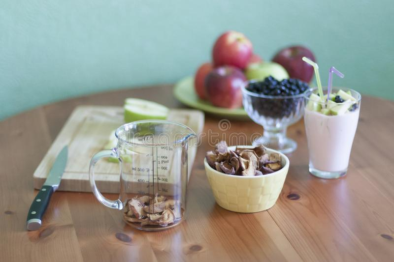 A green bowl of apples, bowl of porridge. Wooden Board with sliced apples. Glass of juice. On the table by the window stock image