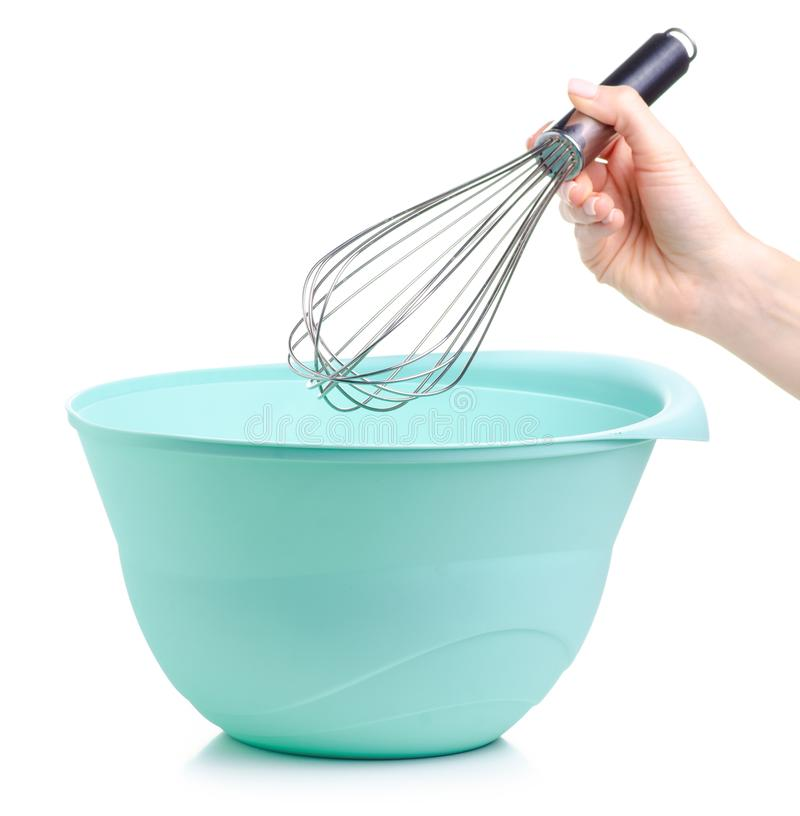 Green bowl and kitchen whisk corolla in hand. On white backgrund isolation stock photos