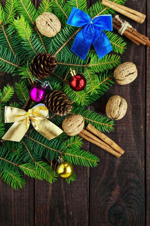 Green branch of fir, decorated with bright ribbons, balls, nuts, pine cones, cinnamon on dark wooden background. royalty free stock photos