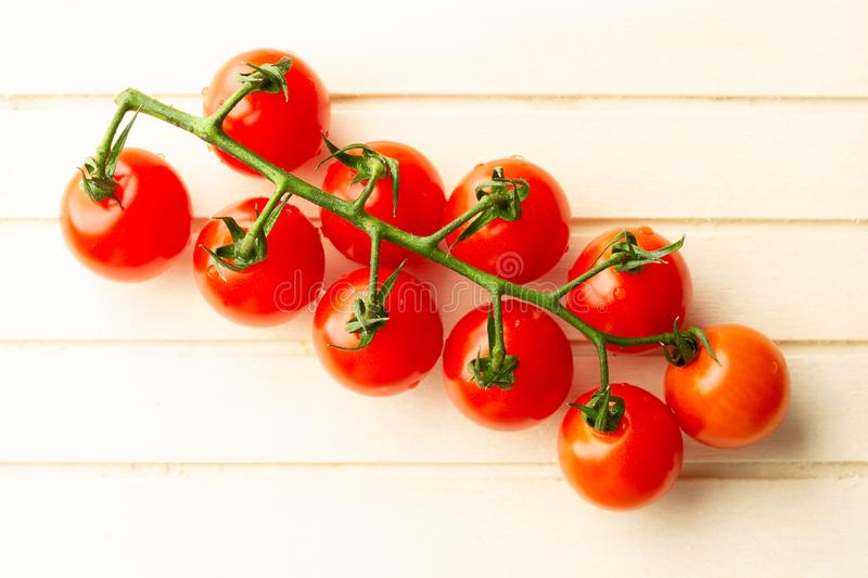 Green branch of red cherry tomatoes on the wooden surface. Top view of the fresh branch of red ripe cherry tomatoes with water drops lying on the wooden striped stock photo