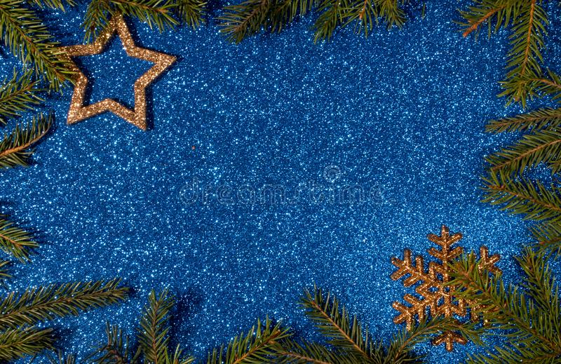 Green branches of spruce on a blue shiny background. New year and Christmas stock photography