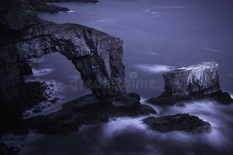 Green Bridge of Wales photographed at night and lit by moonlight. Long exposure image of famous rock formation, natural arch on dramatic coastline of royalty free stock photos