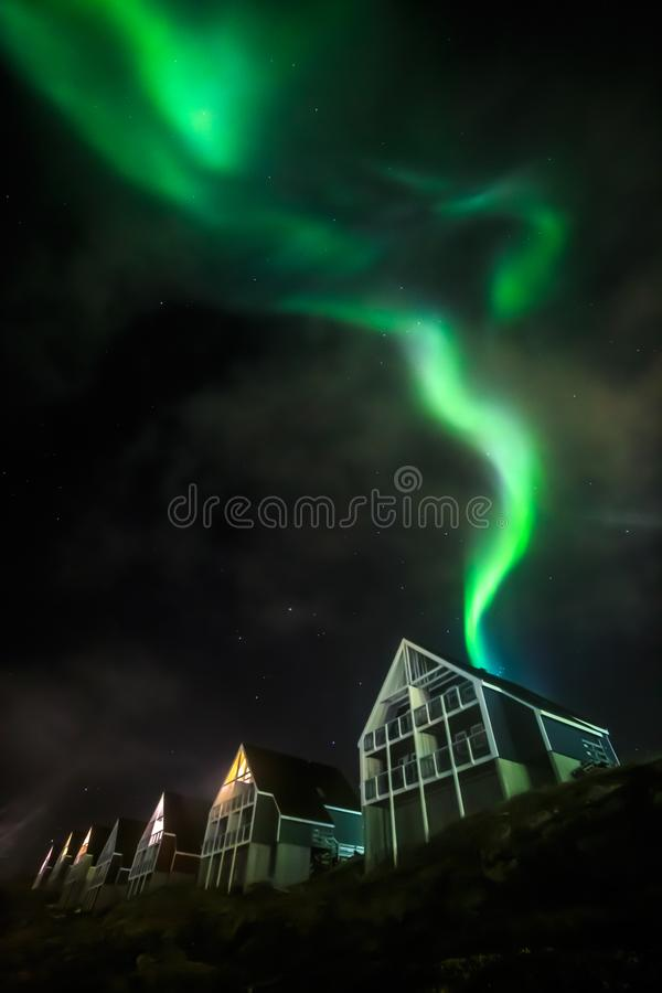 Green bright northern lights partially hidden by the clouds over Inuit living houses, Nuuk city, Greenland royalty free stock photos