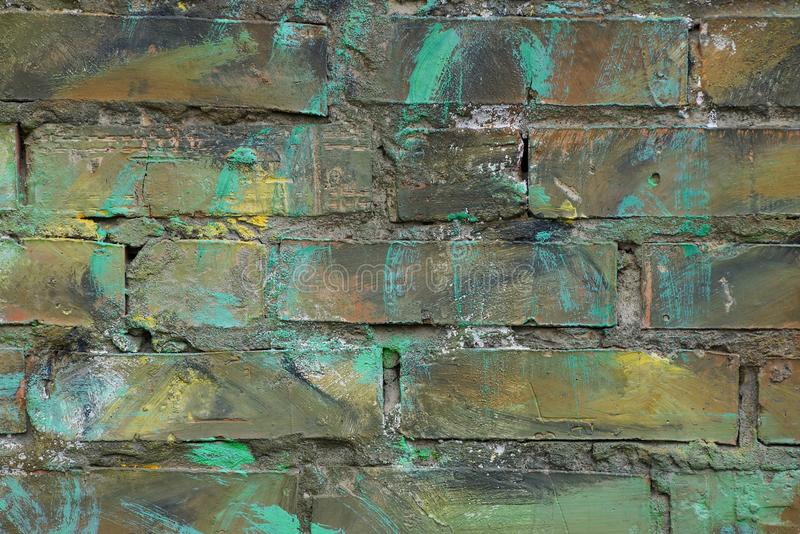 Green brown colored stone background from dirty bricks in a building wall. Green brown colored stone texture of dirty bricks in the wall of a building stock photos