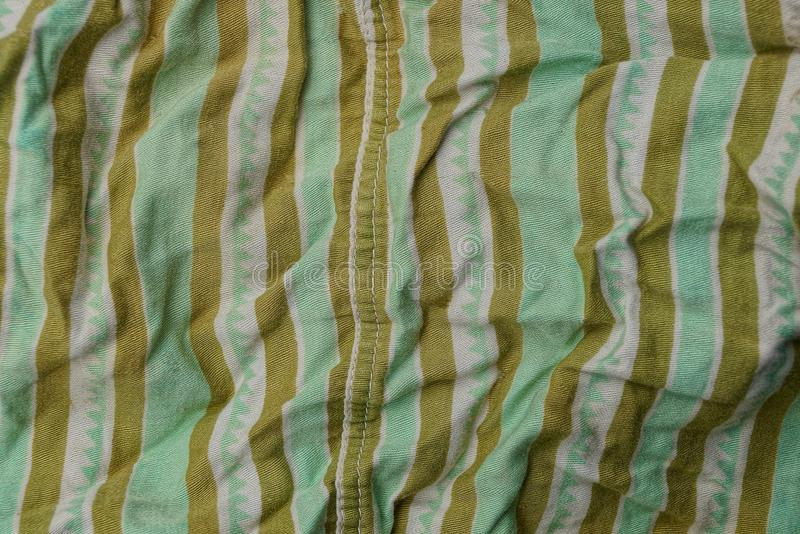 Green brown fabric texture from a piece of crumpled clothes. Green brown fabric background from a piece of crumpled clothes stock photo