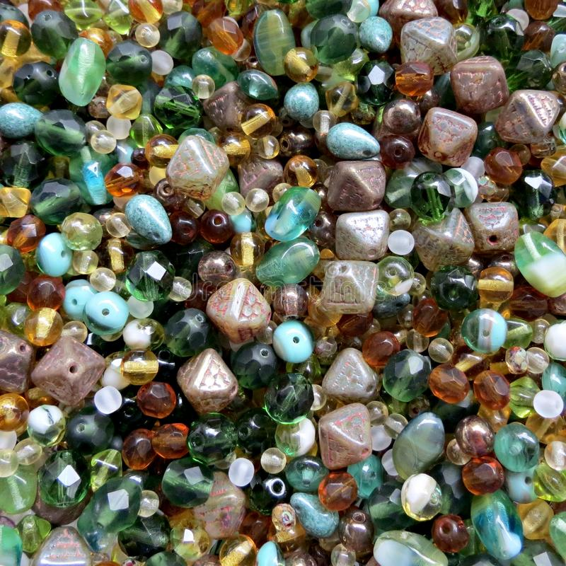 Green and brown glass beads mix for jewellery making. Hobby, handmade jewellery, fine arts. Beads texture. Close up. Green and brown glass beads mix for stock images