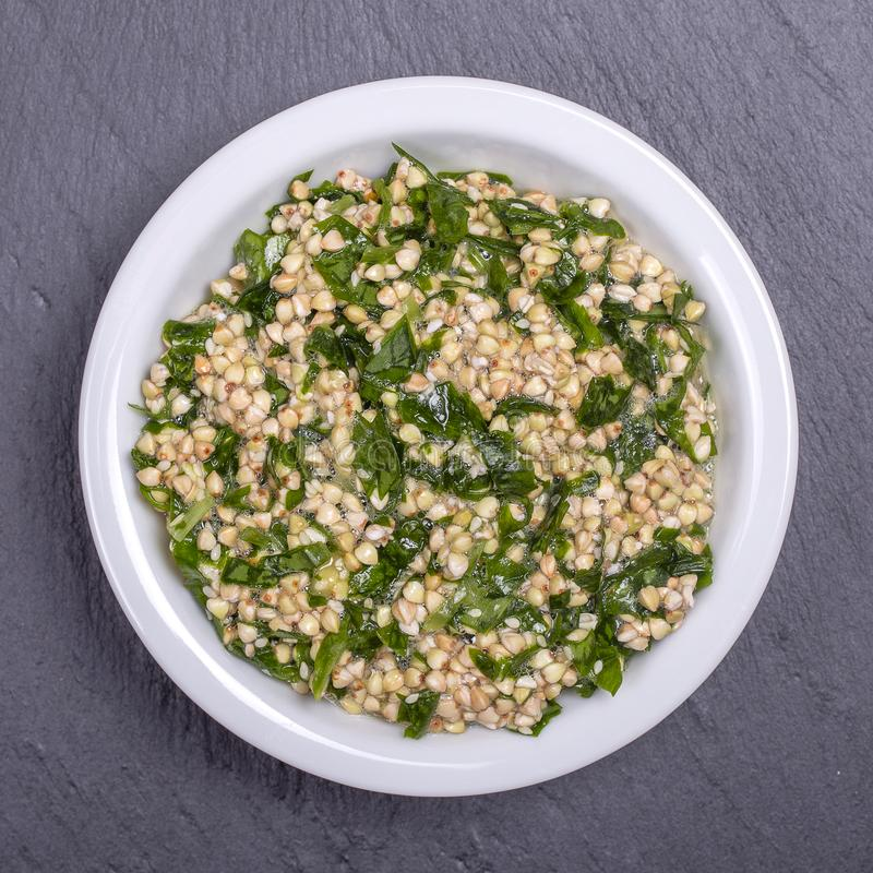 Green buckwheat together with ramson, sesame and honey in white bowl - healthy breakfast food concept, top view. Green buckwheat together with ramson, sesame and stock photos