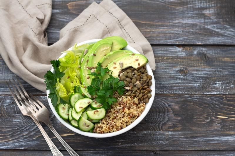 Green Buddha Bowl with lentils, quinoa, avocado, cucumber, fresh lettuce, herbs and seeds. Delicious healthy balanced eating. On a wooden background, top view stock image