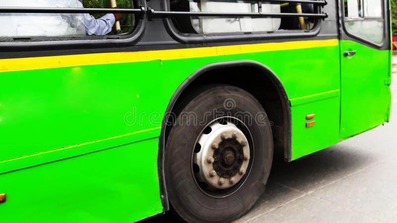 Green bus side closeup view. Wheel, auto, adult, public, interior, steering, transport, car, tour, rapid, cab, tourism, male, profession, school, travel stock image