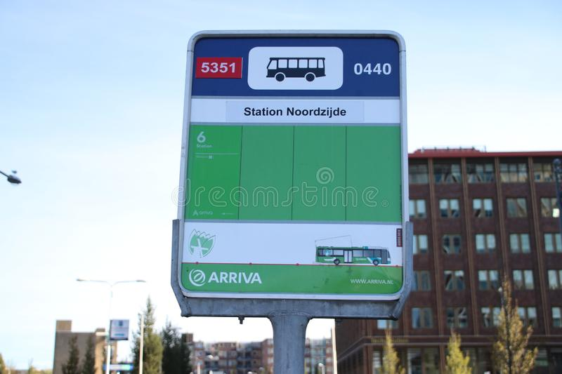 Green bus stop sign of Arriva on the north side of Gouda railway station. stock photography