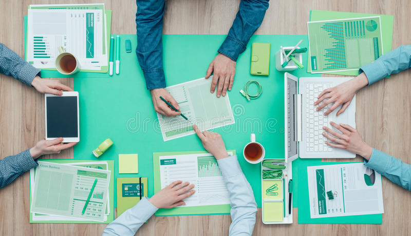 Green business team. Business people working together on a green desktop and examining a report; environment, green business and finance concept stock images