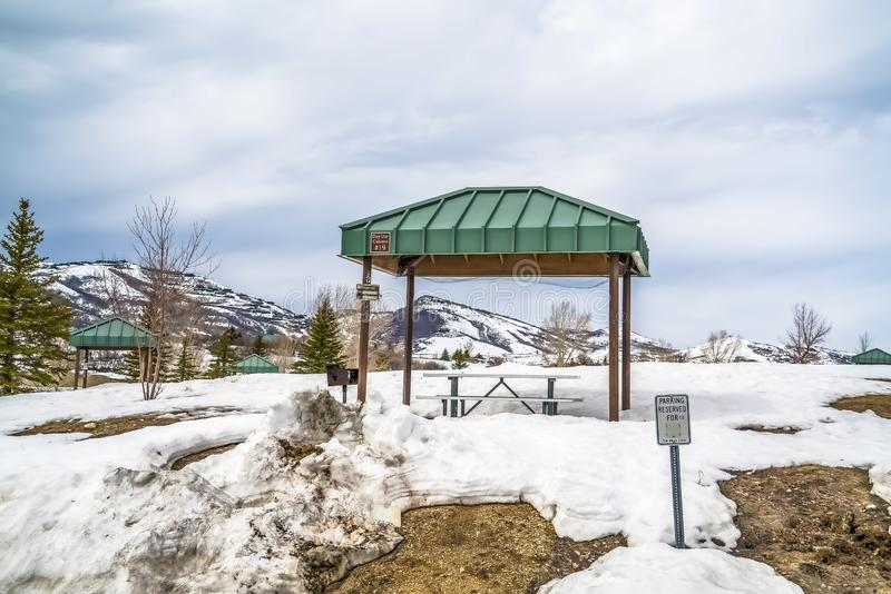 Green cabana with barbecue grill and picnic table at a snow covered park. In the background is a scenic winter view of frosty mountain and cloudy blue sky stock photo