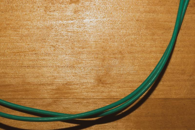 Green cable on a wood background. connection wire lies on the wooden table. Copy space, electric, copper, power, color, energy, line, plastic, electronic stock photos