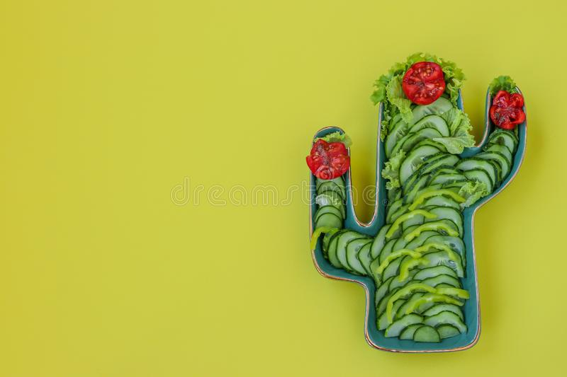 Green Cactus Shaped Dish with fresh salad of tomatoes, cucumbers, pepper and lettuce on yellow background: fiesta party, wild west. Party, copy space stock images
