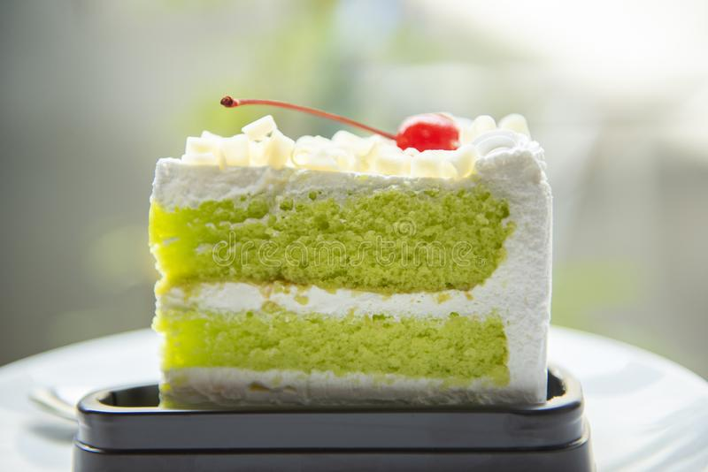 Green cake slice with cherry fruit and cream on white palte on the table - Delicious green tea cheese cake stock photography