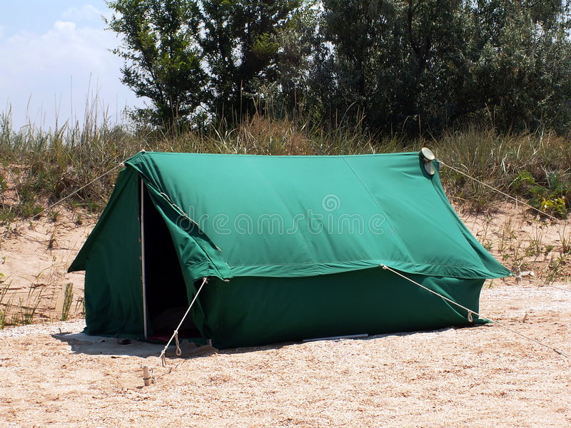 Green Camping Tent. Green retro style camping tent on a beach sand. There is empty aluminum can on the right corner of the tent. There is small forest and patch stock photos