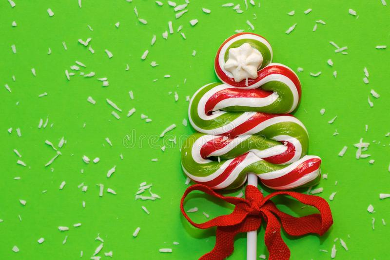 Green candy Christmas tree and snow - desiccated coconut - in front of green background. Let it snow royalty free stock images