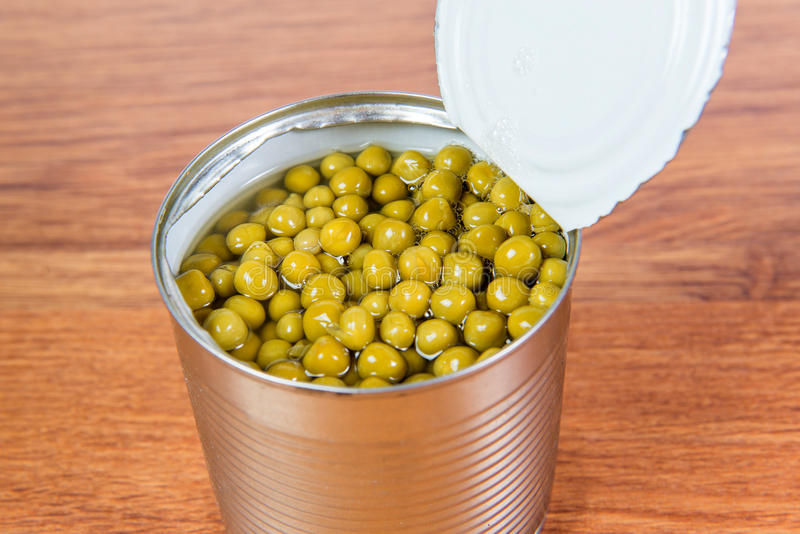 Green canned peas in open iron bank is on the table. stock image