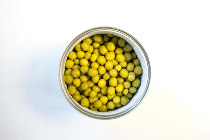Green canned peas in open iron bank is on the table. royalty free stock images