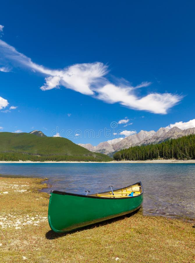 Green Canoe on the shore of a mountain lake stock photo
