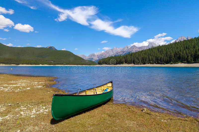 Green Canoe on the shore of a mountain lake stock photos