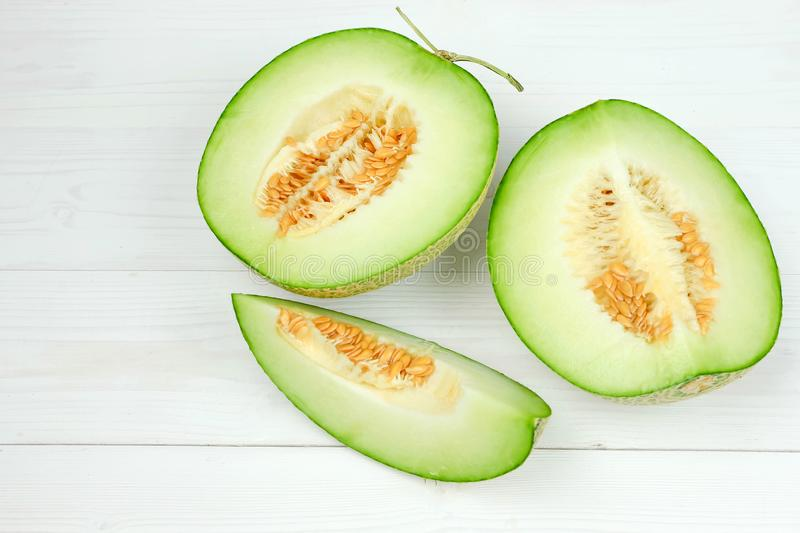 Green cantaloupe melon on white wooden. Top view stock photos