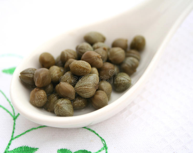 Green capers. Some fresh green capers on a spoon stock photos
