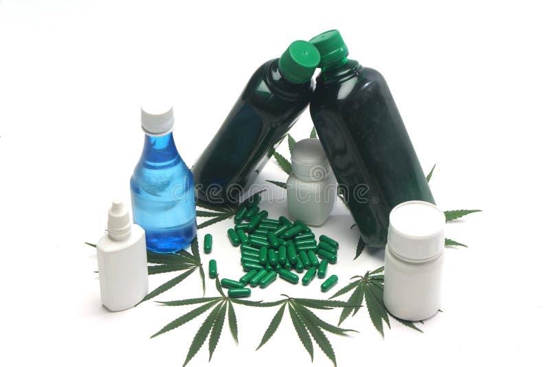 Green capsule, marijuana leaves and bottles. royalty free stock photos