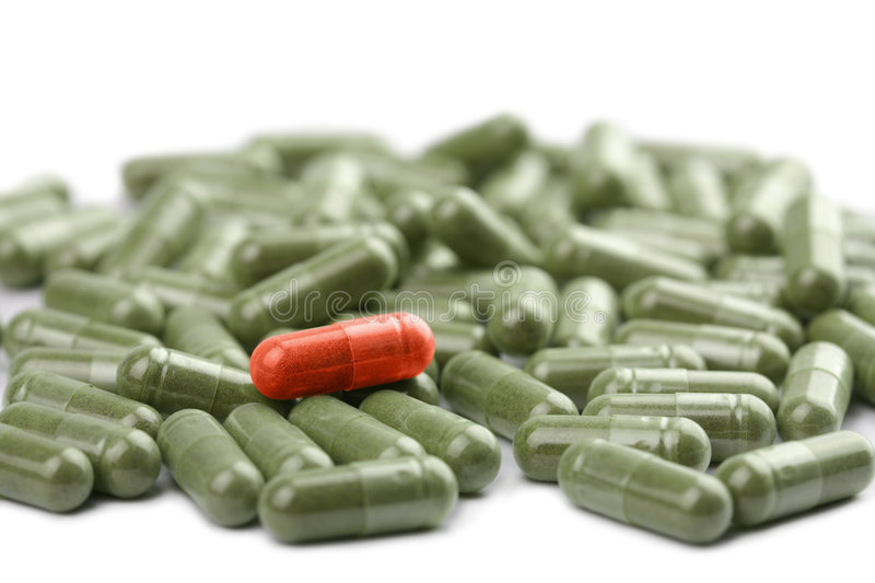 Green capsule pills with red one isolated