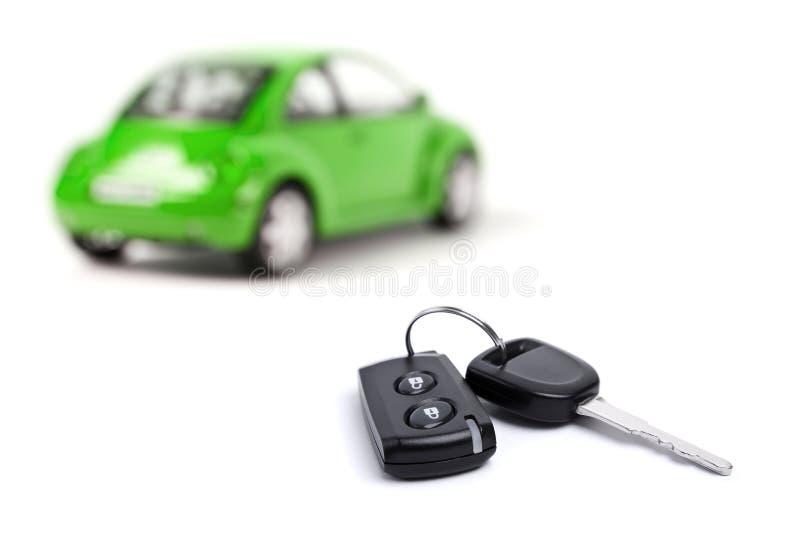 Green car and car key. Green car and a car key on white