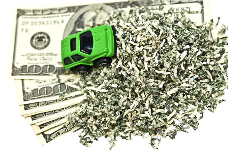 Green Car and Money. A green car driving over a pile of shredded money and some bills. Concept or metaphor for coming out on top by going green stock photos
