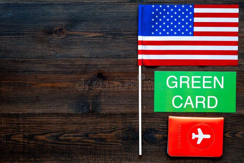 Green Card-Text nahe Passhülle und USA kennzeichnen Draufsicht über dunklen hölzernen Hintergrundkopienraum Immigration zu verein lizenzfreie stockbilder