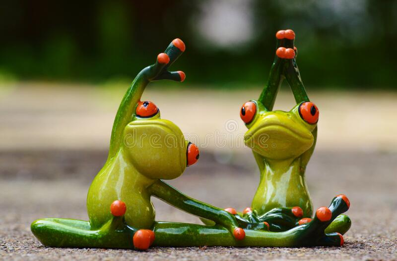Green Ceramic 2 Frog Figurine Doing Exercise royalty free stock image