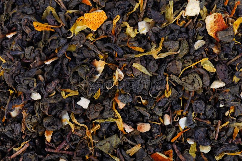 Green Ceylon tea with dry flowers and candied orange background. stock image