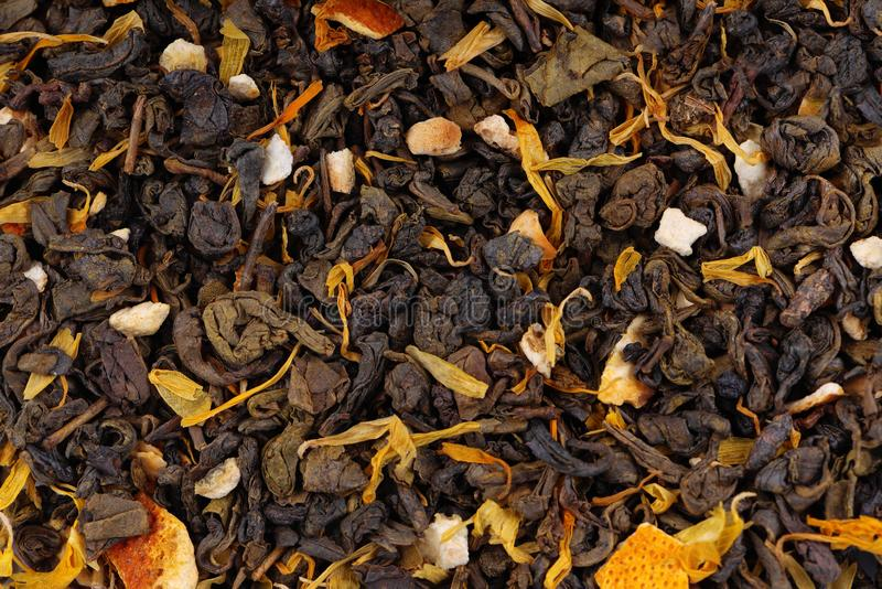 Green Ceylon tea with dry flowers and candied orange background. stock photo
