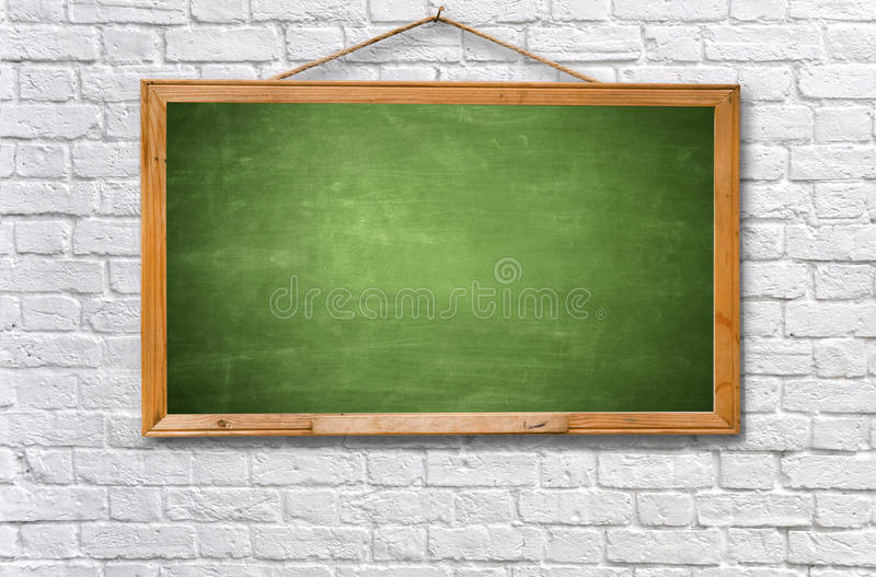Green chalk board on white brick wall. Empty green chalk board on white brick wall texture background stock photography