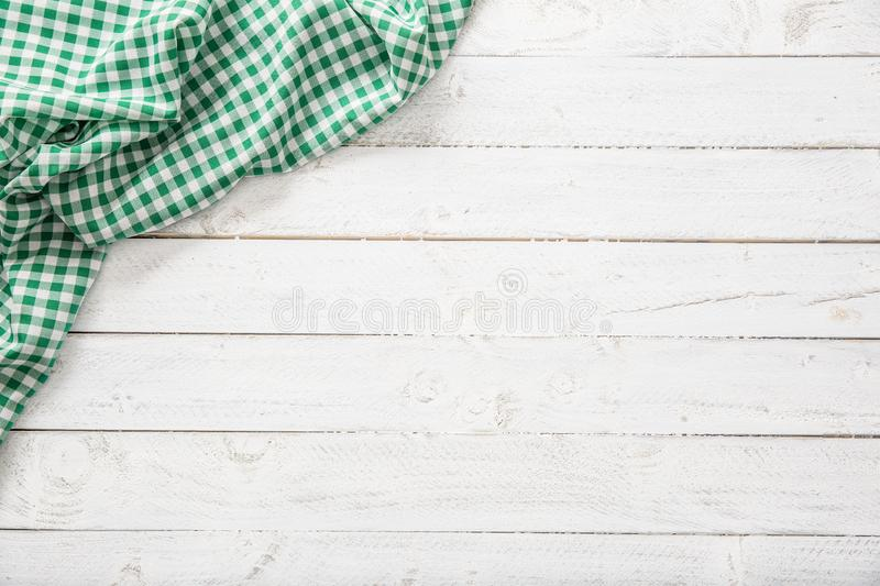 Green checkered kitchen tablecloth on wooden table.  royalty free stock photography