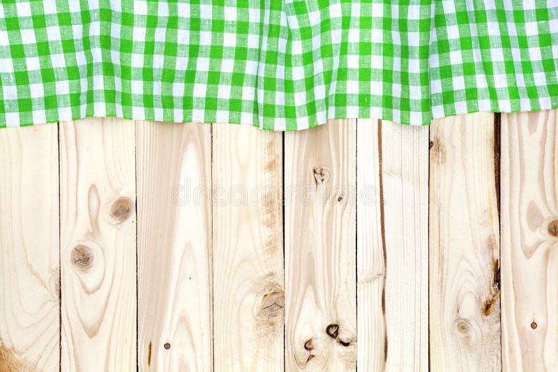 Green checkered tablecloth on wooden table, top view. Green checkered tablecloth on a light wooden table, top view royalty free stock images