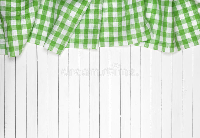 Green checkered tablecloth on wooden table, top view. Green checkered tablecloth on a light wooden table, top view royalty free stock photo
